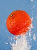 Orange in a jet of water. — Stock Photo