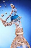 Een splash van water uit een fles. — Stockfoto