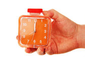 Pomarańczowy budzik w rękę na białym tle. — Zdjęcie stockowe