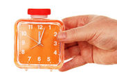 Orange alarm clock in a hand on a white background. — Stock Photo