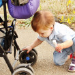 A child playing with a baby carriage. — Stock Photo