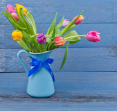 Bouquet of tulips in a blue jug — Stock Photo