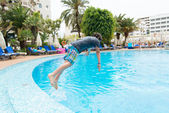 Boy jumping into swimming pool — Stock Photo