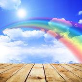 Blå himmel bakgrund med regnbåge och reflektion i vatten. trä pier — Stockfoto