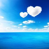 Blue sea under clouds sky with heart shape cloud background — Stock Photo