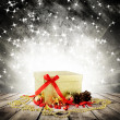 Royalty-Free Stock Photo: Golden christmas gift box with christmas balls on wood planks over red blured background with light and stars