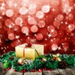 Golden christmas gift box with christmas balls on wood planks over red blured background with light and stars — Stock Photo #14403185