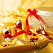 Golden gift with red bow on silk with rays and star. Christmas background — Stock Photo