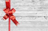 červené vánoční luk na grunge dřevěné pozadí s prostorem pro text — Stock fotografie