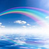 Blå himmel bakgrund med regnbåge och reflektion i vatten — Stockfoto
