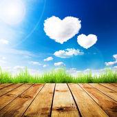 Groen gras op houten plank over een blauwe lucht met hart vorm wolken. — Stockfoto