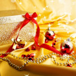 Golden gift with red bow on silk with rays and star.  — Stock Photo
