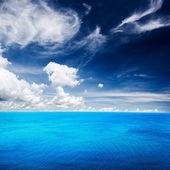 Blauwe zee onder wolken hemel — Stockfoto