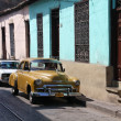 People walk past old car in Santiago, Cuba. — Stock Photo