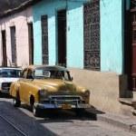 People walk past old car in Santiago, Cuba. — Stock Photo