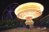 Amusement park at night - ferris wheel and carousel — Stock Photo
