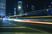 Light trails on modern building background in shanghai china — Stock Photo