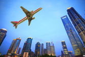 Samoloty latające nad miasto nowoczesne budynki — Zdjęcie stockowe