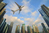 Aircraft flying over the modern city buildings — Stock Photo