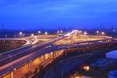 Modern city with highway overpass in sunset night scene — Stock fotografie