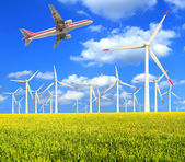 Aircraft is flying in the rice farms Modern wind turbines — Стоковое фото