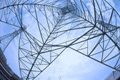 查找高电压电力塔在太阳的天空 — 图库照片