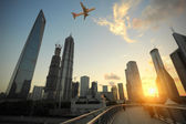 Shanghai,Aircraft is flying in the modern urban buildings — Stock Photo