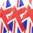 UK flags hanging on the gold flagstaff — Stock Photo #27602425