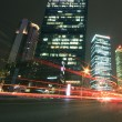 Modern office building background of car night with light trails — Stock Photo #27604023