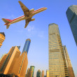 Aircraft flying over the modern city buildings — Stock Photo #27604131