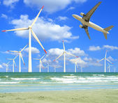 Aircraft is flying in eco power of wind turbines — Stock Photo