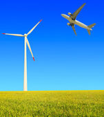Aircraft is flying in the rice farms Modern wind turbines — Stock Photo