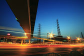 Long exposure of cars passing through of transmission tower — Stock Photo