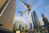 Aircraft flying over the modern city buildings over — Stock Photo