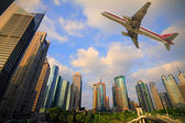 Aircraft flying over the modern city buildings over — Foto Stock