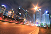 The light trails on modern office building background in shangha — Stock Photo