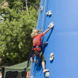 Little blondie girl training on an outdoor climbing tower  — Stock Photo