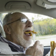Senior man with expressive face eating  fast foods  — Stock Photo
