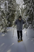 Aged senior with snowshoes — Stock Photo