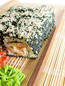 Sushi rolls with black roe and sesame on bamboo mat — Stock Photo