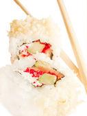 Roll sushi dwoma pałeczkami nad białym — Zdjęcie stockowe