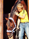 Little boy with horse in stable — Stock Photo
