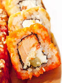 Sushi rolls in range on the desk closeup isolated on white — Stock Photo