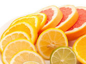 Ripe citrus slices on plate isolated on white — Stock Photo