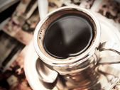 Cup of hot coffee at vintage napkin — Stock Photo