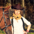 Beautiful cowgirl with her red horse — Stock Photo