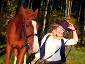 Nice young cowgirl with her red horse. — Stock Photo