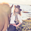 Cute cowgirl with her horse at gulf. — Stock Photo #13618417