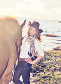 Cute cowgirl with her horse at gulf. — Stock Photo