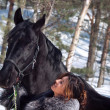 Nice women with black horse. winter — Stock Photo
